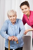 stock photo of crutch  - Nurse with elderly woman walking on crutches - JPG