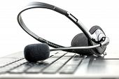 image of conversation  - Headset lying on a laptop computer keyboard conceptual of telemarketing call center client services or online support - JPG