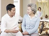 foto of mother law  - asian mother and adult son chatting on couch - JPG
