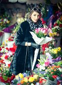 foto of flower shop  - Beautiful brunette woman with gloves choosing flowers at the florist shop. Fashionable female with sunglasses and head scarf at flower shop. Pretty brunette in black choosing flowers - urban shot