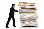 stock photo of paper cut out  - Stock image of businessman pushing a giant stack of documents isolated on white background - JPG