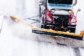 stock photo of plowing  - Snowplow Truck Removing the Snow from the Highway during a Cold Snowstorm Winter Day - JPG