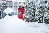 pic of snow shovel  - Woman Shoveling her Parking Lot after a Snowstorm - JPG