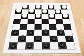 foto of draught-board  - Starting position on vinyl 8x8 draughts board on wooden table - JPG