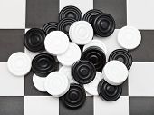 stock photo of draught-board  - pile of draughts on black and white checkerboard - JPG