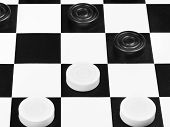 stock photo of draught-board  - draughts game on black and white board close up - JPG