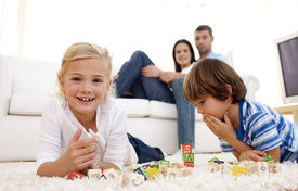 foto of children playing  - Children playing with alphabet cubes at home with parents on sofa - JPG