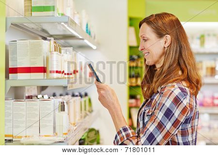 Woman scanning barcode of cosmetics in supermarket with her smartphone