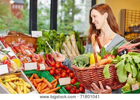 Smiling elderly woman with shopping list buying groceries and vegetables in a supermarket