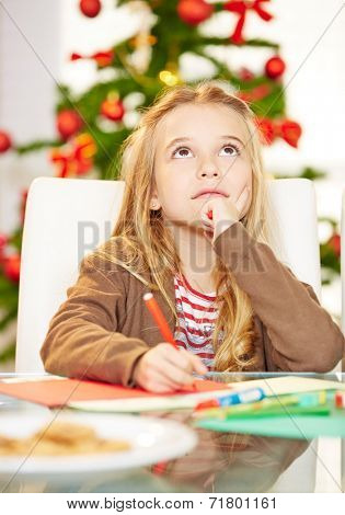 Pensive child writing wishlist to Santa Claus for christmas
