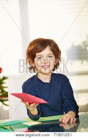 Happy boy giving card with wishlist for christmas