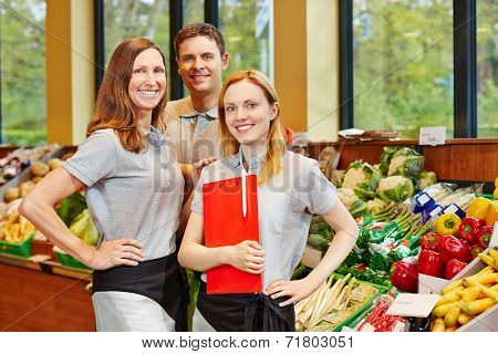 Team of smiling store manager and happy salespeople in a supermarket