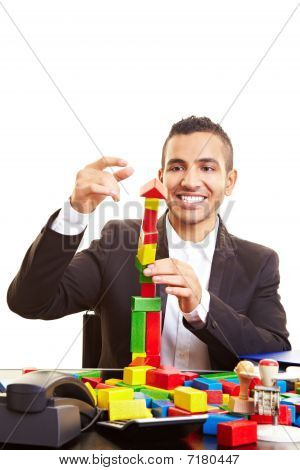 Businessman Having Fun With Building Bricks
