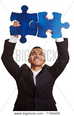 Businessman Solving Huge Jigsaw Puzzle