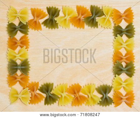 Tri Color Bow Tie Pasta Border on Wooden Background