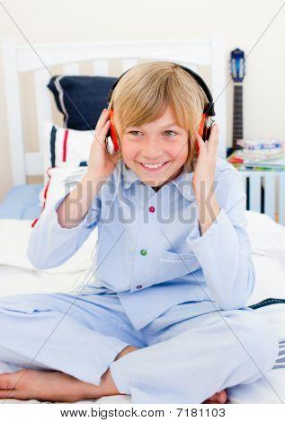 Menino positivo ouvir música sentado na cama