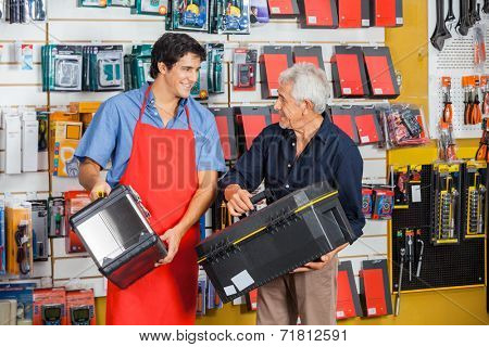 Senior man looking at young salesman while selecting toolbox in hardware store