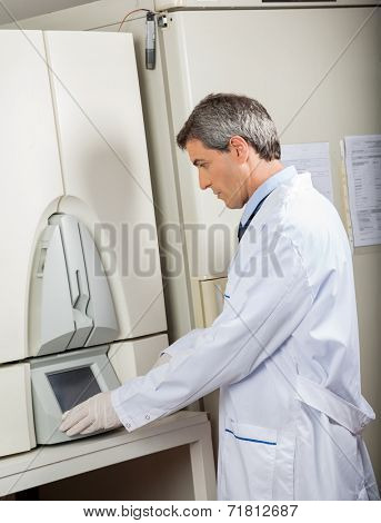Side view of mature male scientist using blood culture instrument in lab