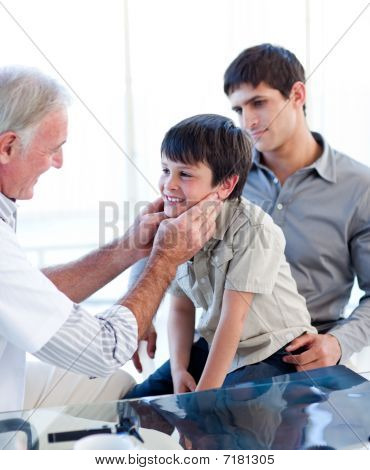 Senior Doctor Examing Little Boy Throat With His Father