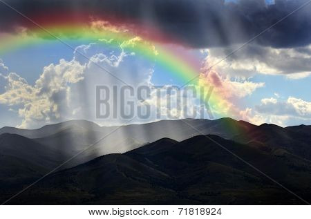 Sunlight rays from clouds falling on dark mountain range with Rainbow
