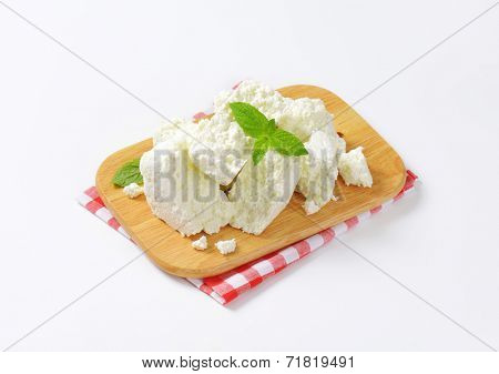 slices of fresh cheese on wooden cutting board and checkered dishtowel