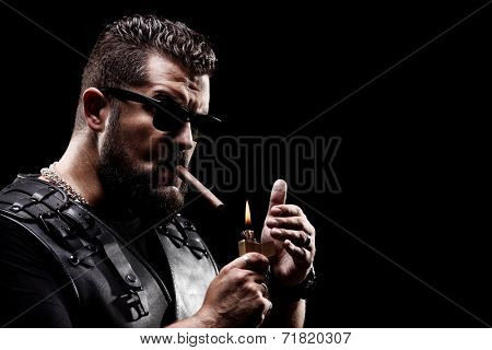 Badass biker lighting up a cigarette on black background
