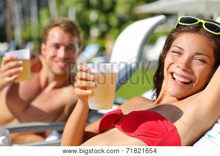 People drinking beer at relaxing at beach resort having fun enjoying spring break. Young couple relaxing drinking alcoholic drink on summer vacation holidays travel.