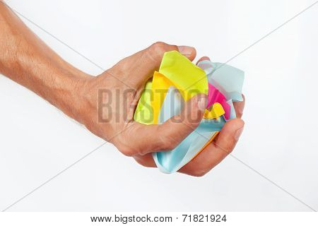 Hand grasps the crumpled paper trash on white background