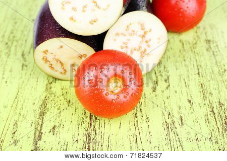 Incised eggplants and tomatoes on wooden background