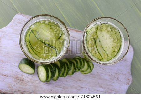 Glasses of cucumber cocktail on cutting board on wooden background