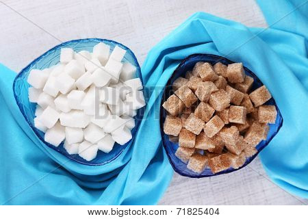 White and brown Refined sugar in color bowls on wooden background