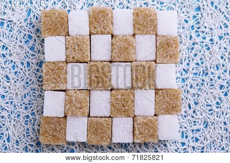 Brown and white refined sugar on light background