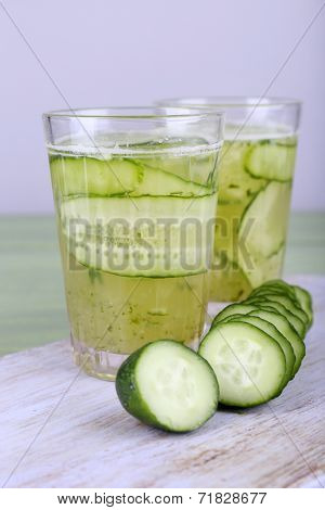Glasses of cucumber cocktail on cutting board on wooden table on light background
