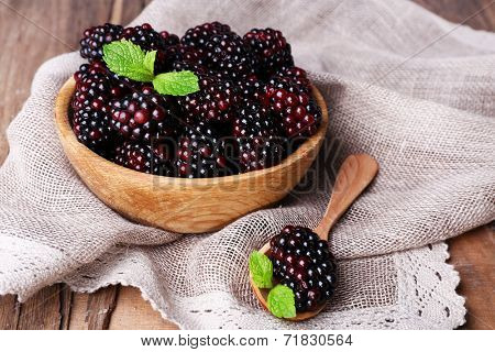 Wooden bowl of blueberries on sacking napkin on wooden background closeup