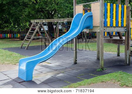 Blue toboggan in the middle of a playground without children