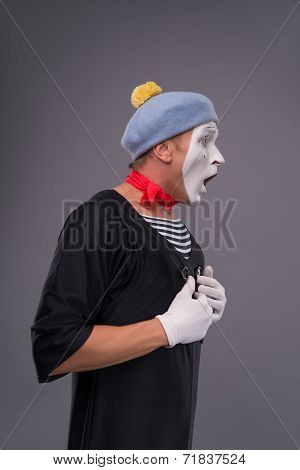 Portrait of male mime in red head and with white face isolated o