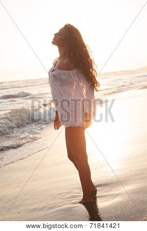 young woman enjoy in sun and water on sandy beach by the sea full body shot at sunset