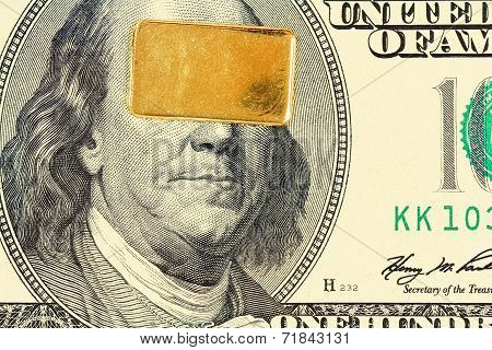 Gold bar over dolar banknote