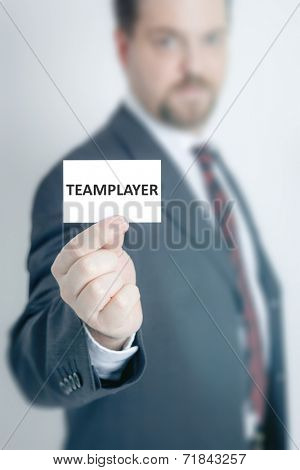 A business man holding a card with the word team-player