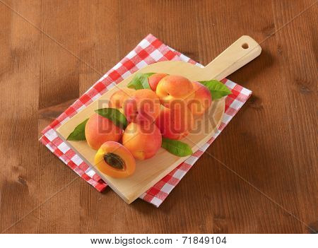 heap of ripe apricots on wooden cutting board and checkered dishtowel