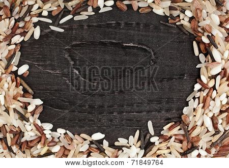 Frame made of colorful blend of rice varieties : brown rice, mixed wild rice, white (jasmine) rice in a rustic wooden surface background