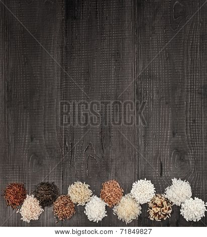 Border of colorful varieties of whole grain rice in a rustic wooden surface background