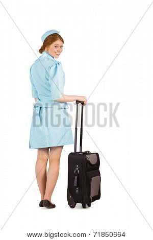 Pretty air hostess leaning on suitcase on white background