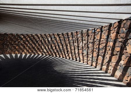 Pavilion of stone and concrete with geometric shadow