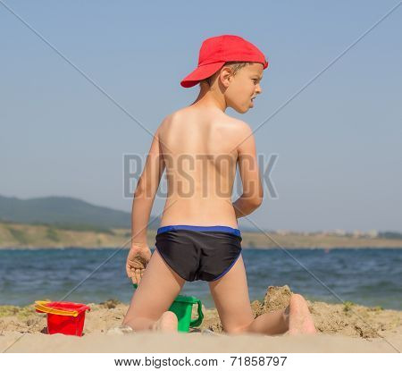 Astonished boy on the beach with his back staring