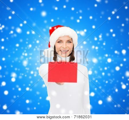 christmas, holdays, people, advertisement and sale concept - happy woman in santa helper hat with blank red card over blue snowy background