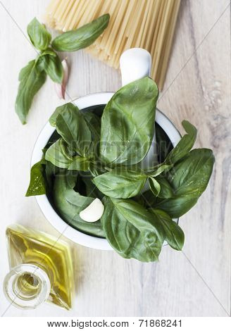 Ingredients for Pesto alla Genovese on wooden background - basil, parmesan, garlic, olive oil