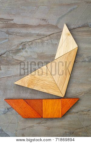 abstract picture of a sailing yacht built from seven tangram wooden pieces over a slate rock background, artwork created by the photographer