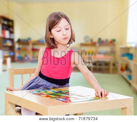 Charming girl sits at a table