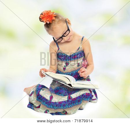 The little girl in big glasses reading a book